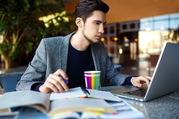 Disparo de joven estudiante masculino sentado en la mesa y escribir en el cuaderno. joven estudiante masculino estudiando en la cafetería.