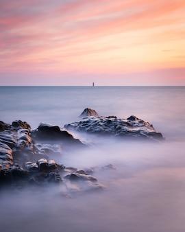 Disparo de larga exposición del paisaje marino en guernsey durante una puesta de sol