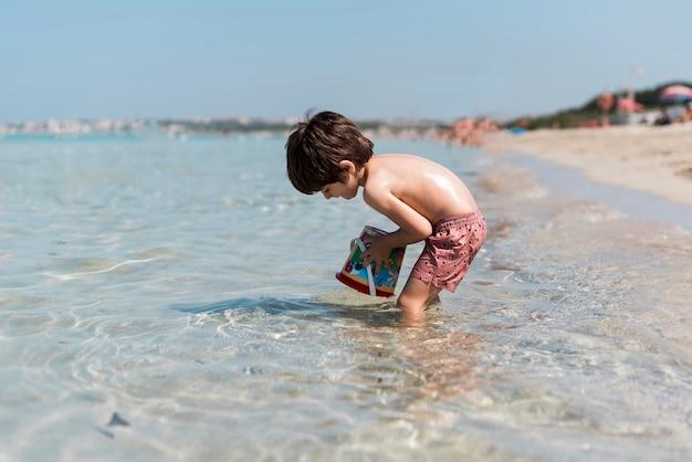Disparo lateral de un niño jugando en el agua.