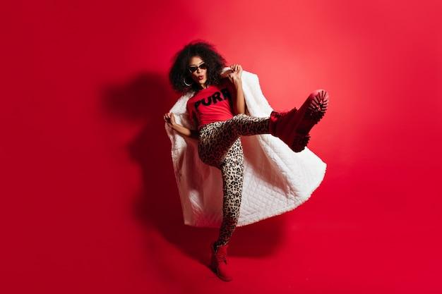 Disparo de longitud completa de adorable mujer divertida saltando sobre pared roja