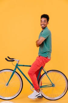 Disparo de longitud completa de chico negro seguro sentado en su bicicleta con los brazos cruzados. retrato de hombre africano complacido relajante.
