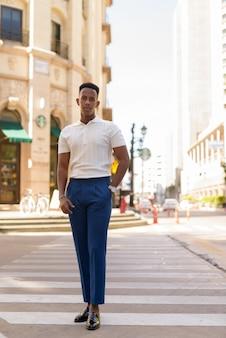 Disparo de longitud completa del joven empresario africano al aire libre caminando sobre el paso de peatones