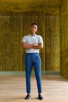 Disparo de longitud completa del joven empresario africano sonriendo al aire libre contra la pared de bambú con los brazos cruzados