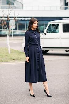 Disparo de longitud completa de muy hermosa joven en elegante vestido negro y bombas negras sobre fondo de ciudad. concepto de estilo y moda