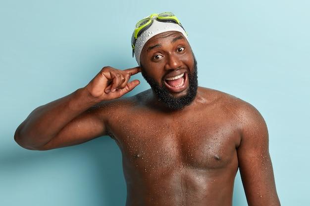 Disparo de media longitud de feliz hombre afroamericano tiene agua en la oreja después de bucear, piel oscura húmeda, abre la boca ampliamente