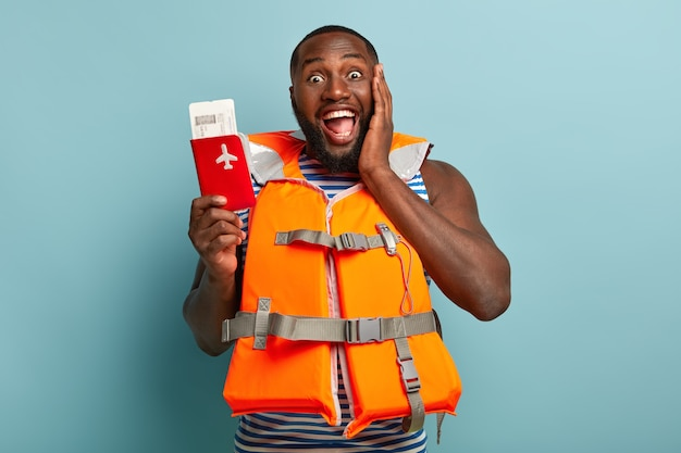 Disparo de media longitud del hombre negro feliz disfruta de los próximos viajes, tiene pasaporte rojo con boletos, comparte impresiones