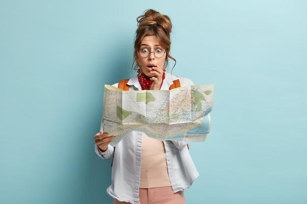 Disparo de media longitud de una mujer asustada y avergonzada que mira estresadamente el mapa, tiene miedo de perderse, usa gafas ópticas