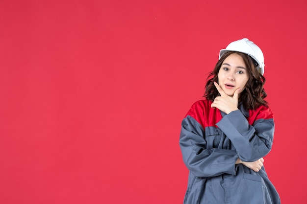 Disparo de medio cuerpo de confiado constructor femenino en uniforme con casco y concentrado en algo sobre fondo rojo aislado