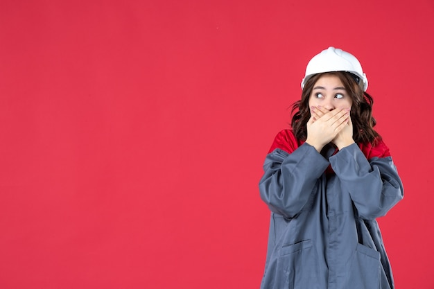 Disparo de medio cuerpo de conmocionado constructor femenino curioso en uniforme con casco sobre fondo rojo aislado