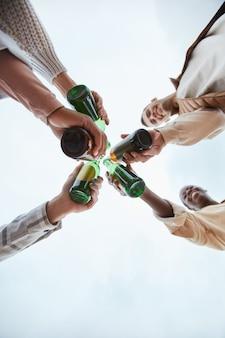 Disparo mínimo de jóvenes tintineando botellas de cerveza y brindando contra el cielo, espacio de copia