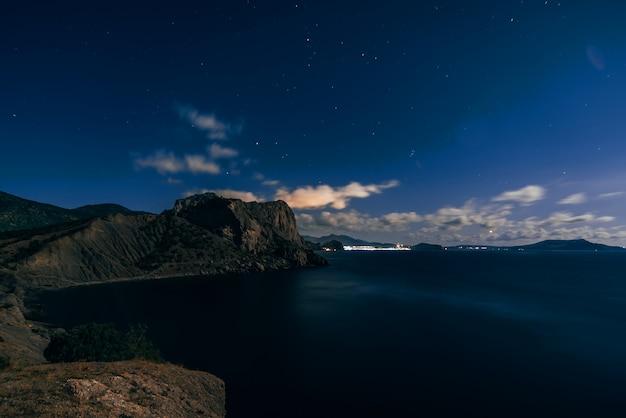 Disparo nocturno del estrellado cielo azul oscuro, montañas y mar en el pueblo de novy svet