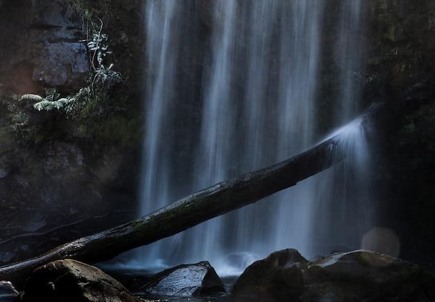 Disparo oscuro de una cascada que cae fuertemente sobre rocas y chapoteando en un palo de madera