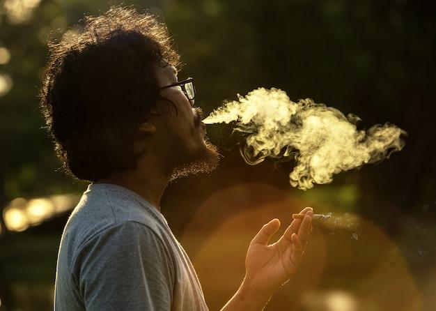 Disparo oscuro y sombrío de un hombre fumando
