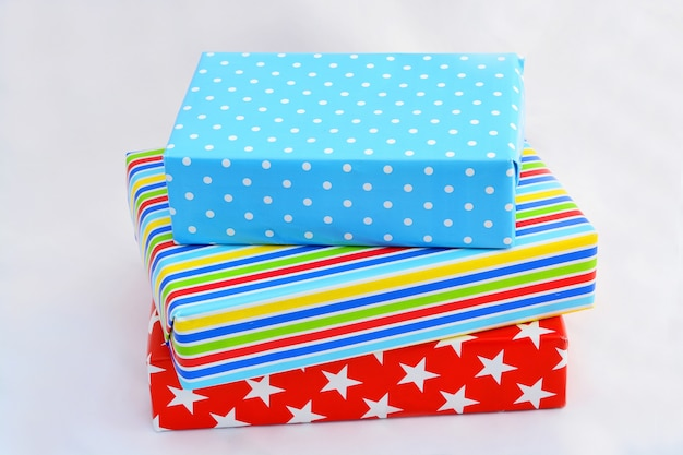 Disparo de primer plano aislado de cajas de regalo en envoltorios coloridos apilados encima de cada uno sobre fondo blanco.