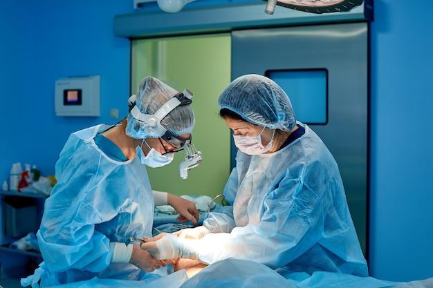 Disparo en la sala de operaciones, el asistente entrega instrumentos a los cirujanos durante la operación. los cirujanos realizan la operación. médicos que realizan cirugía.