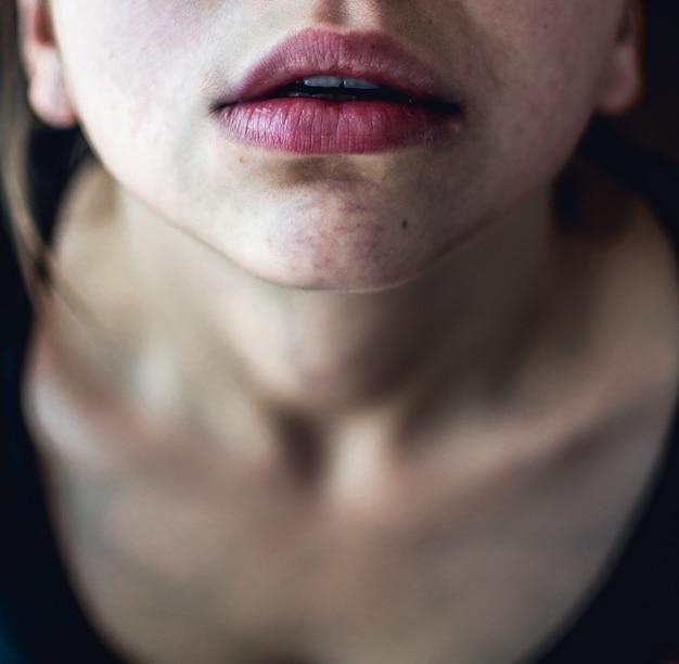 Disparo selectivo de cerca de arriba de una mujer con piel pálida y labios rosados secos mirando hacia arriba