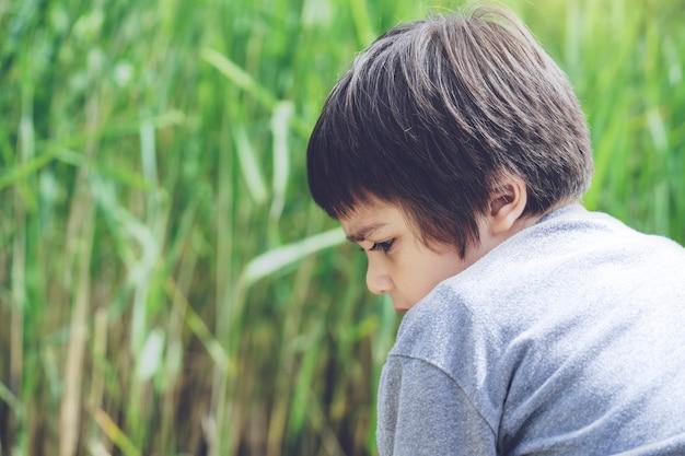 Disparo sincero vista trasera niño sentado solo con campos de hierba borrosa, cabeza corta niño mirando hacia abajo con cara curiosa, little oby teniendo aventura en la reserva natural en primavera o verano