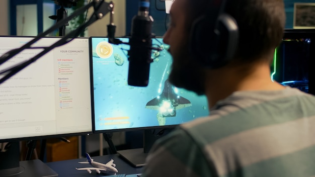 Disparo trasero del hombre streamer jugando en un poderoso videojuego de disparos por computadora para el torneo, hablando con varios jugadores en auriculares