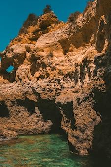 Disparo vertical de un acantilado rocoso reflejándose en el mar en un día soleado