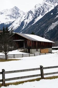 Disparo vertical de un albergue de madera cubierto de nieve y montañas en invierno