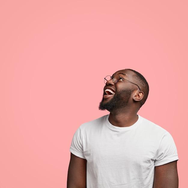 Disparo vertical de alegre hombre sin afeitar de piel oscura mira positivamente hacia arriba, estando de buen humor,