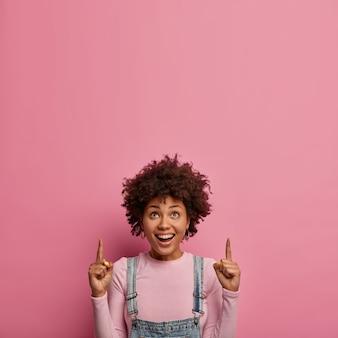 Disparo vertical de una alegre mujer étnica con puntos de pelo afro arriba, demuestra un impresionante espacio de copia, tiene una expresión de rostro alegre, muestra dientes blancos, se viste informalmente, promociona un artículo en un centro comercial o tienda