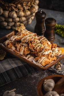 Disparo vertical de alitas de pollo deliciosamente cocidas con salsa en la mesa bajo las luces