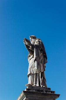 Disparo vertical de una antigua estatua histórica tocando el cielo azul claro