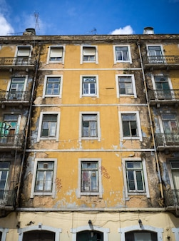 Disparo vertical de un antiguo edificio de apartamentos pintado de amarillo con algunas ventanas rotas