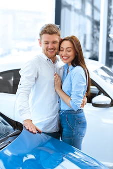 Disparo vertical de un apuesto hombre abrazando a su novia feliz sonriendo alegremente mientras toca un auto nuevo en el concesionario