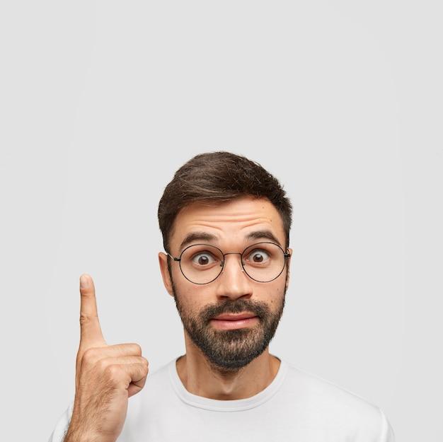 Disparo vertical de asombrado joven hipster hombre apunta con el dedo índice hacia arriba