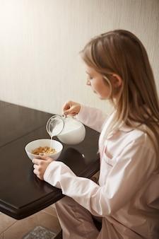 Disparo vertical de la atractiva hija rubia sentada en un acogedor pijama en la cocina, vertiendo leche en un tazón con cereales, desayunando sola, preparándose para estudiar en la universidad