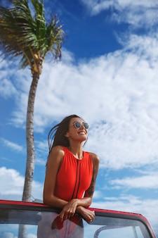 Disparo vertical de una atractiva modelo femenina en un traje de baño rojo, se para en el coche, se apoya en el parabrisas de un coche y sonríe.