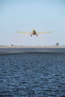 Disparo vertical de un avión monomotor vintage con una hélice sobrevolando un paisaje agrícola