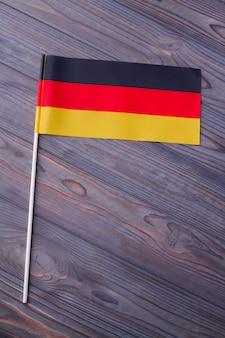 Disparo vertical de la bandera de alemania en el escritorio de madera gris