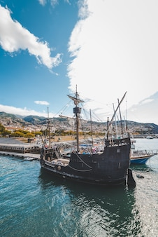 Disparo vertical de un barco de madera en el agua cerca del muelle en funchal, madeira, portugal.