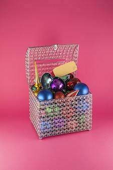 Disparo vertical de una caja llena de coloridos juguetes para árboles de navidad