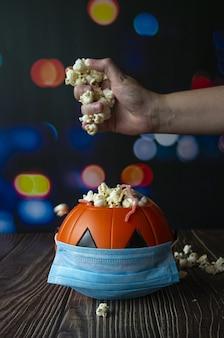 Disparo vertical de una calabaza de halloween con palomitas de maíz y una mascarilla sanitaria