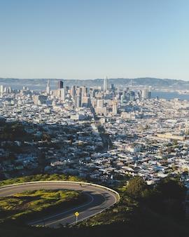 Disparo vertical de una carretera con curvas cuesta abajo con los edificios de la ciudad en la distancia bajo un cielo azul