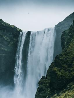 Disparo vertical de la cascada skogafoss en islandia en un día sombrío
