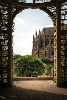 Disparo vertical del castillo y la catedral de arundel desde un hermoso arco cubierto de follaje verde