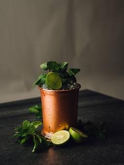 Disparo vertical de un cóctel mojito i una taza de cobre con hojas de limón y menta alrededor