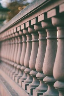 Disparo vertical de columnas de valla de un puente bajo la luz del sol con un fondo borroso