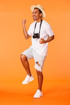 Disparo vertical de cuerpo entero hombre parado en la terminal del aeropuerto con pantalones cortos, camiseta blanca, bomba de puño triunfante y mirando la esquina superior izquierda como ver un partido de fútbol, ganar, naranja