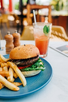 Disparo vertical de una deliciosa hamburguesa y unas papas fritas y una copa de cóctel en la mesa