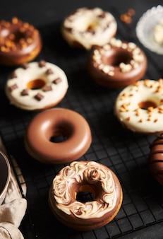 Disparo vertical de deliciosas donas cubiertas con el glaseado de chocolate blanco y marrón sobre un cuadro negro