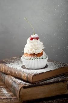 Disparo vertical de un delicioso cupcake con crema y cereza en la parte superior de los libros