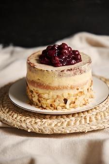 Disparo vertical de un delicioso pastel de cereza con crema en una placa blanca.