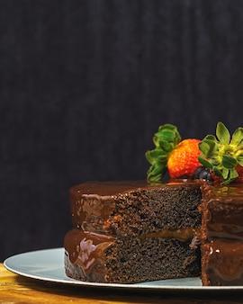 Disparo vertical de un delicioso pastel de chocolate decorado con fresas y arándanos