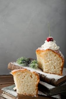 Disparo vertical de un delicioso pastel con crema, azúcar en polvo y cerezas en libros